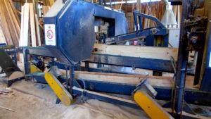 Portada, maquina cortando tablas de madera, Maderas San Juan